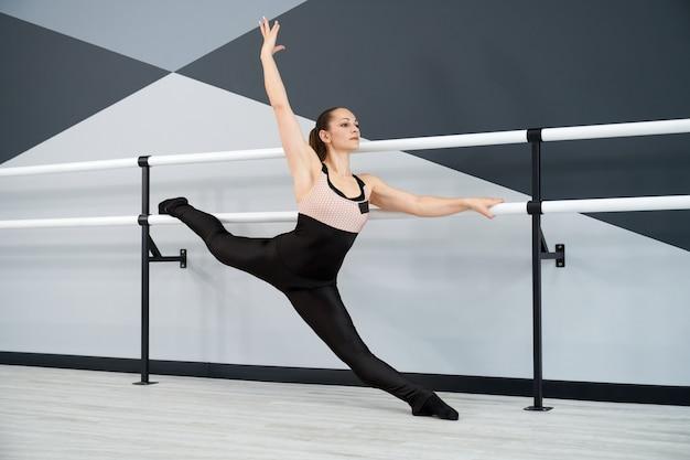 Vrouw benen strekken op leuningen in dansstudio