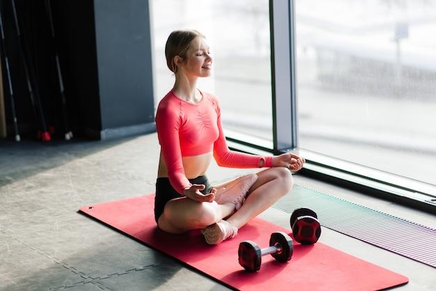Vrouw beoefenen van geavanceerde yoga op mat tegen een groot raam