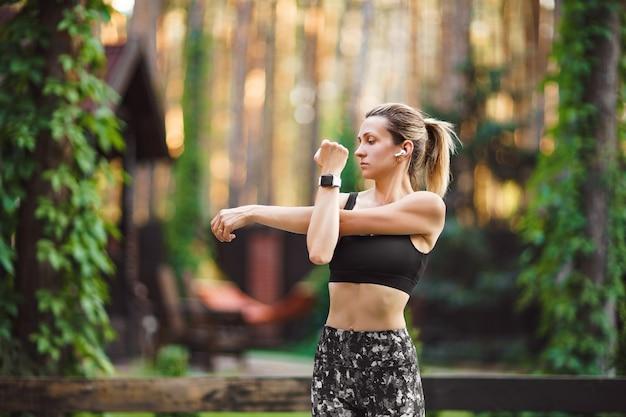 Vrouw beoefenen van ochtendyoga en die zich uitstrekt in de achtertuin. gezonde levensstijl.