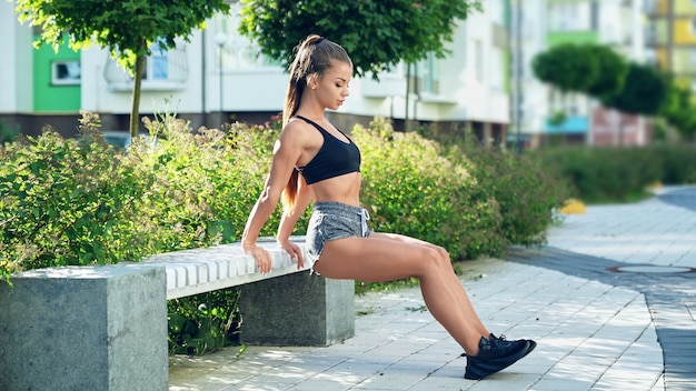 Vrouw beoefenen van oefening op triceps op bank.