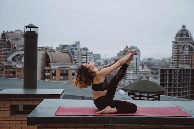 Vrouw beoefenen van yoga op de mat op het dak en het doen van yoga-oefeningen