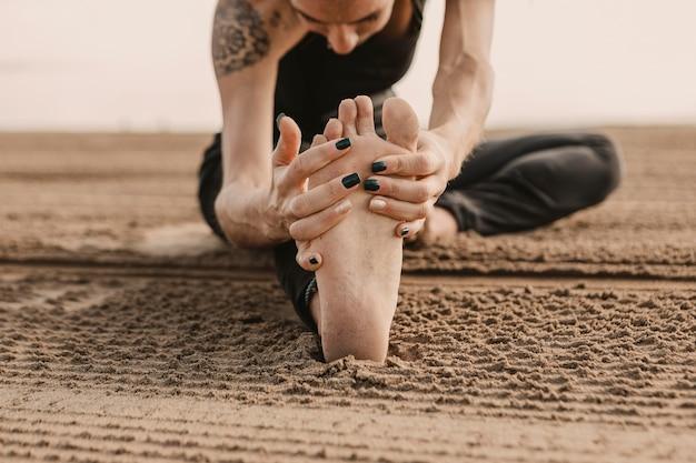 Vrouw beoefenen van yoga op het strand tijdens het strekken van haar been