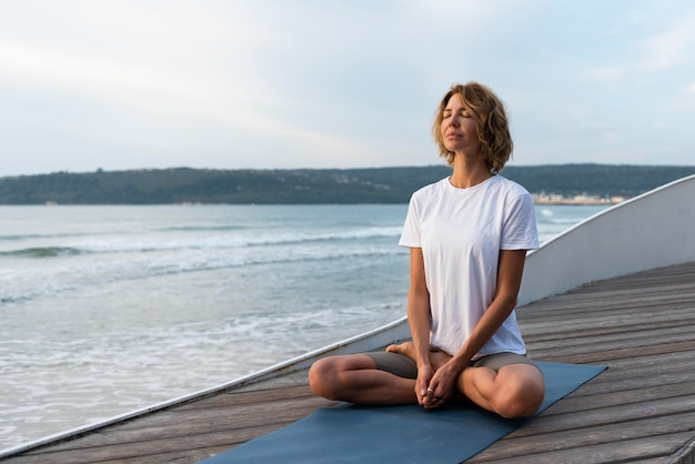 Vrouw beoefenen van yoga pose in de buurt van zee