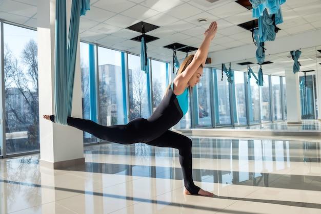 Vrouw beoefent aerial yoga in hangmat. anti-zwaartekracht ontspannend soort sport. gezondheid, vlieg yoga concept.
