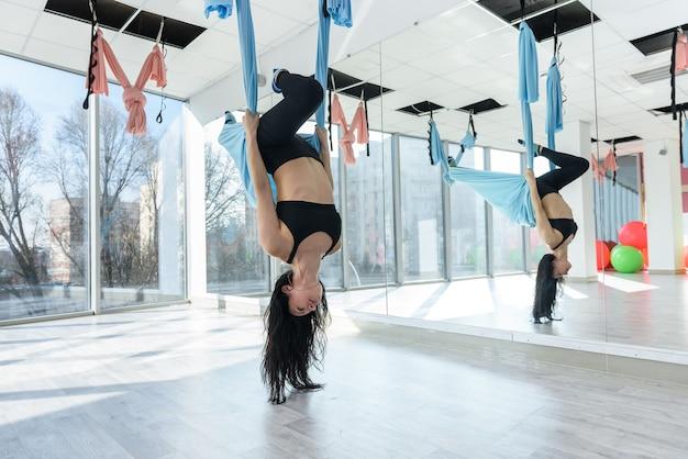 Vrouw beoefent anti-zwaartekracht vlieg yoga met hangmat in fitness-studio. ontspan oefening voor een gezonde levensstijl