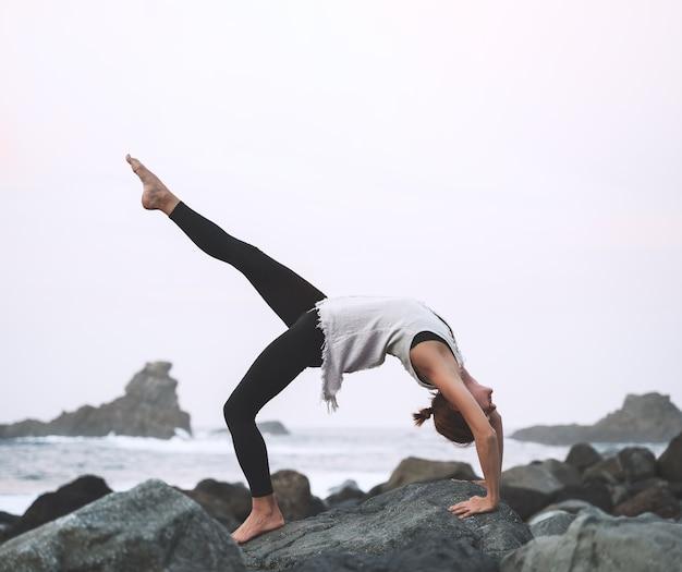 Vrouw beoefent yoga en meditatie op het prachtige wilde strand