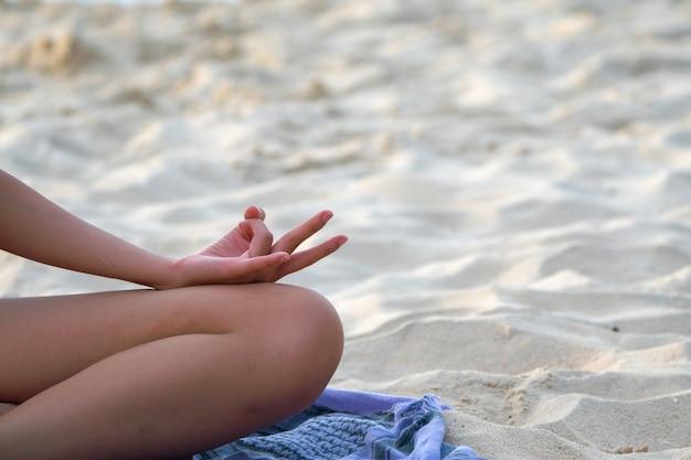 Vrouw beoefent yoga en mediteert op het strand