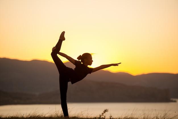 Vrouw beoefent yoga in de bergen aan de oceaan.
