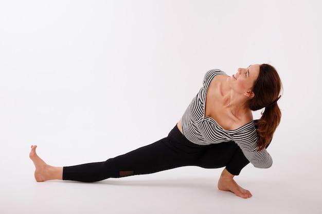 Vrouw beoefent yoga in zwarte legging op een witte geïsoleerde achtergrond. internationale yogadag
