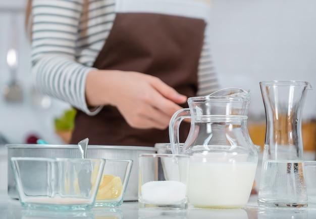 Vrouw bereidt bakkerijingrediënten op aanrechttafel in de keuken met het water van het melkei en bloem.