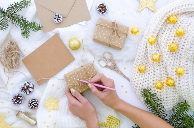 Vrouw bereidt geschenken voor op kerst, wikkelt ambachtelijk papier en maakt unieke handgemaakte dozen