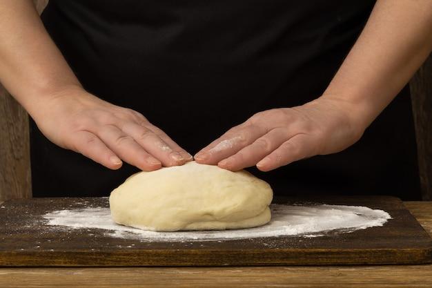 Vrouw bereidt gistdeeg voor pizza of brood