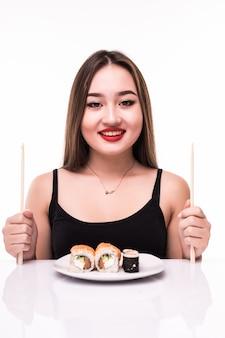 Vrouw bereidt klaar om te eten sushi broodjes smaak met behulp van houten stokjes geïsoleerd op wit