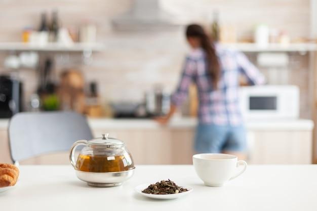 Vrouw bereidt ontbijt in de keuken en aromatische kruiden voor hete thee