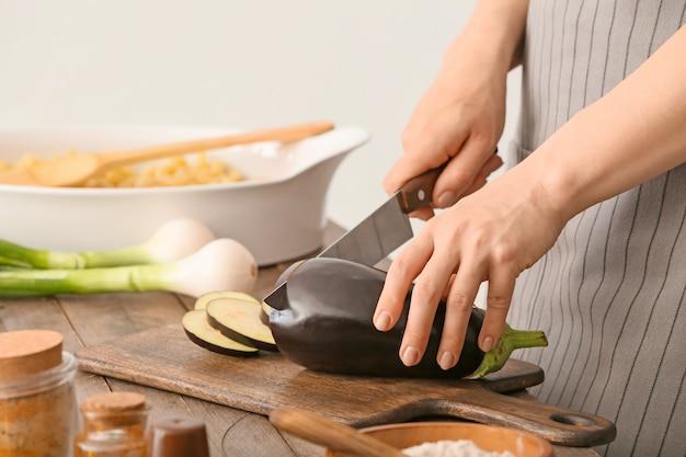 Vrouw bereidt smakelijke pasta in ovenschaal op tafel