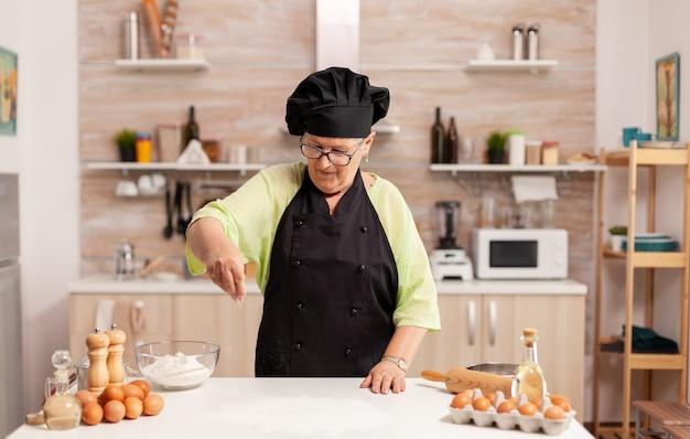 Vrouw bereidt smakelijke pizza die bakpoeder op de keukentafel bestrooit. gelukkige bejaarde chef-kok met uniform besprenkelen, zeven met de hand zeven van ruwe ingrediënten.
