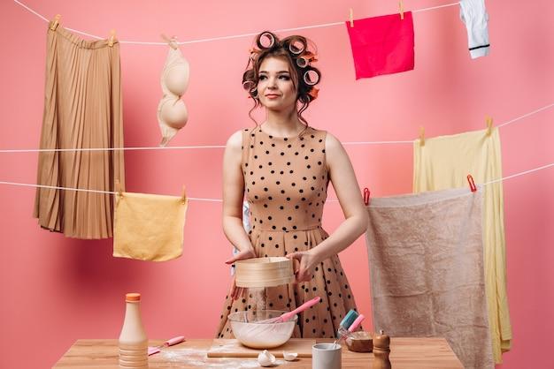 Vrouw bereidt voedsel, ze zeeft bloem door een zeef. mooie huisvrouw is bezig met huishoudelijke taken op een roze achtergrond.