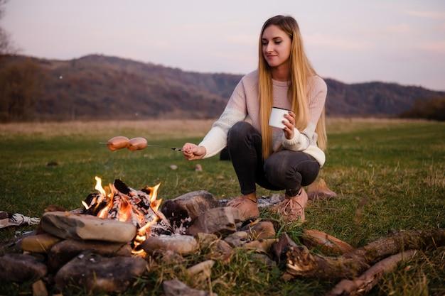 Vrouw bereidt worstjes op een metalen spies op een vuur