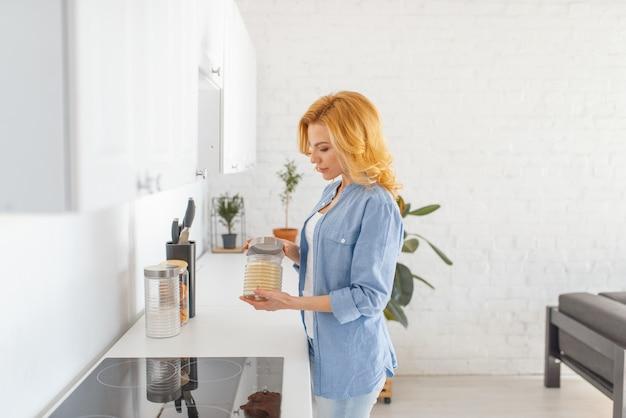 Vrouw bereidt zich voor om het ontbijt op de keuken te koken