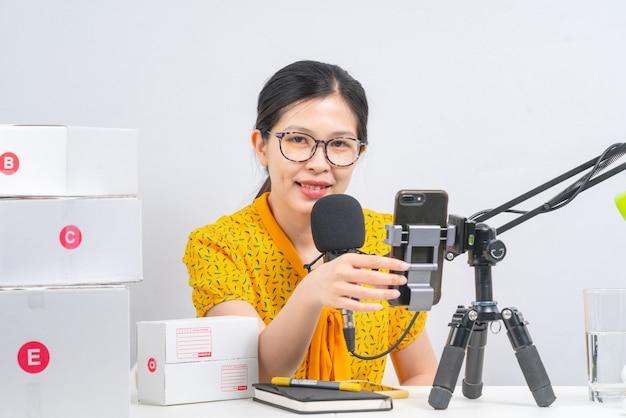 Vrouw bereidt zich voor op levering aan klanten en met behulp van een microfoon