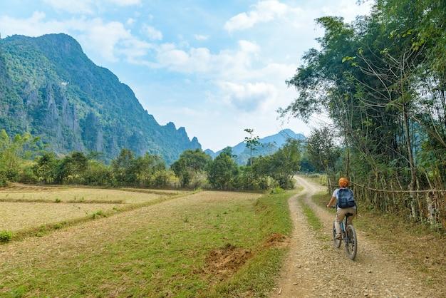Vrouw berijdende mountainbike op onverharde weg in schilderachtig landschap rond vang vieng