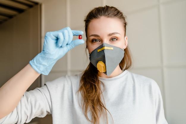 Vrouw beschermend masker dragen en handschoenen die rode pil houden