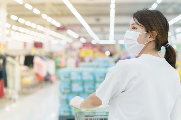 Vrouw beschermt zichzelf tegen infectie met het chirurgische masker en handschoenen, met een winkelwagentje om te winkelen in de supermarkt na een pandemie van het coronavirus.