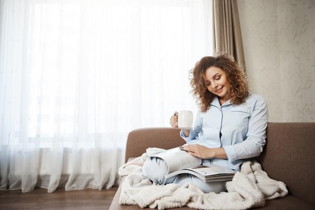 Vrouw besloot zichzelf op een goede dag te behandelen. portret van aantrekkelijke vrouwelijke krullend haar zittend op de bank in pyjama, koffie drinken, genieten van het lezen van tijdschrift, voeten met deken