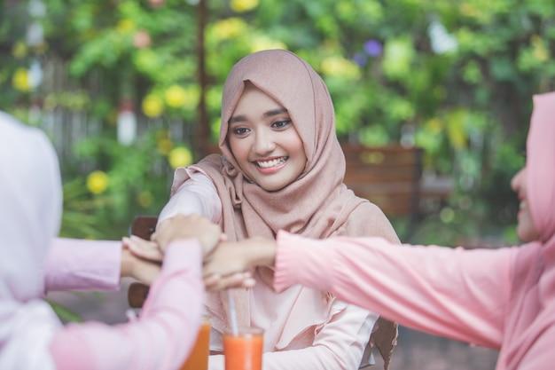Vrouw beste vrienden handen samenbrengen in café