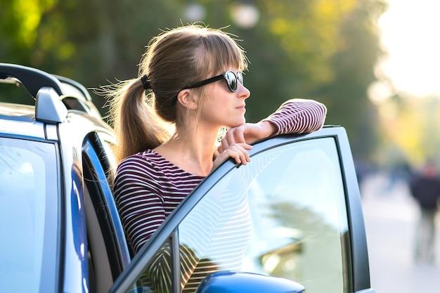 Vrouw bestuurder in casual outfit genieten van warme dag in de buurt van haar auto op een zomerse straat