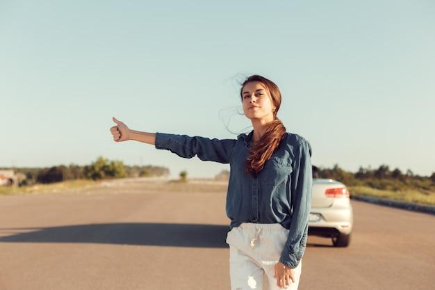 Vrouw bestuurder in de buurt van een kapotte auto, een auto op een landweg, een vrouw vangt een ritje