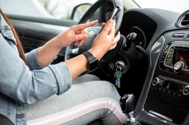 Vrouw bestuurder met behulp van een gsm, smartphone tijdens het besturen van haar auto, gevaarlijk concept