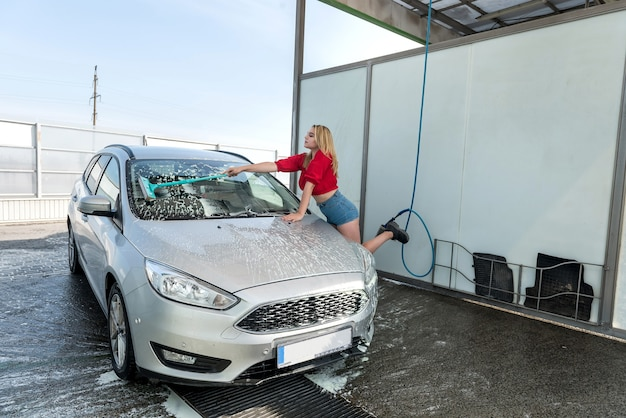 Vrouw bestuurder schuimt haar auto met borstel bij handmatige car wash station