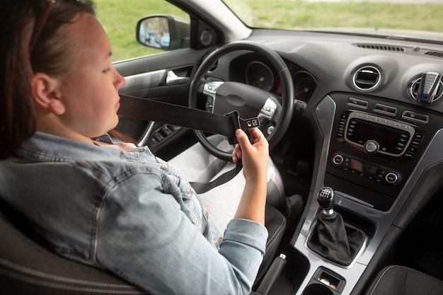 Vrouw bestuurder vastmaken van de veiligheidsgordel voor haar rijden, veilig rijden concept