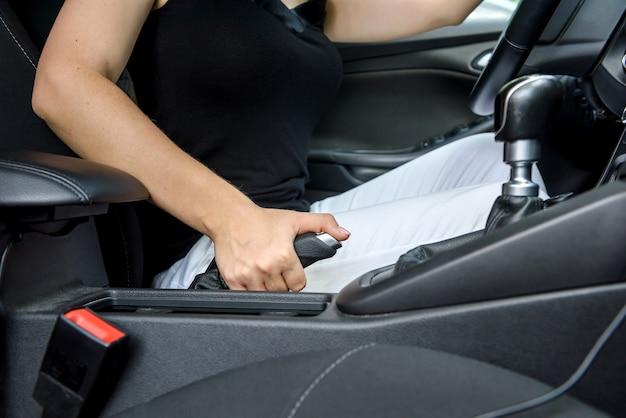 Vrouw bestuurder zit in de auto en stuurwiel te houden