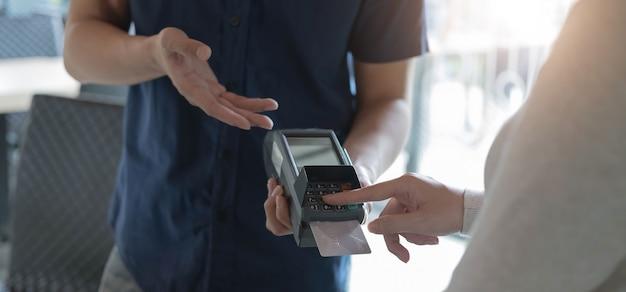 Vrouw betaalt met creditcard en voert pincode in op lezer die in koffie wordt vastgehouden. klant die creditcard gebruikt voor betaling. volwassen kassier die betaling via nfc-technologie accepteert.