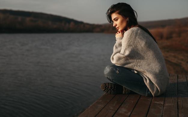 Vrouw bewonderen uitzicht op meer bij zonsondergang