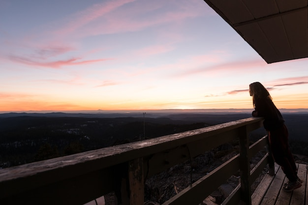 Vrouw bewondert de adembenemende zonsondergang over de groene bossen