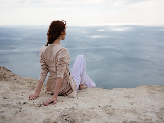 Vrouw bewondert de oceaan rotsachtige stenen romantiek ontspanning