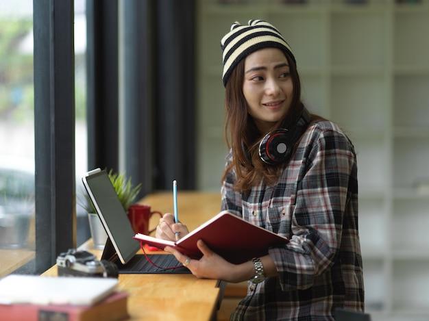Vrouw bezig met haar opdracht tijdens het schrijven op laptop in comfortabele werkruimte