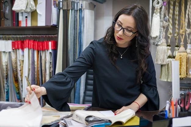 Vrouw bezit een winkel met interieurstoffen en decor