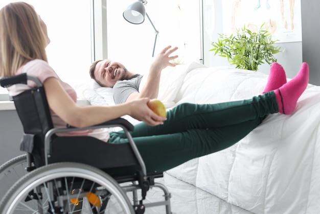 Vrouw bezoeker zittend in een rolstoel in de buurt van de patiënt in bed. bezoek aan zieke patiënten concept