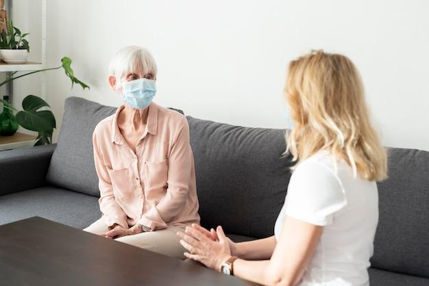 Vrouw bezoekt haar oudere familielid in het verpleeghuis
