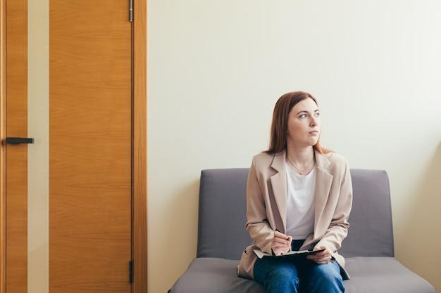 Vrouw bezorgd in de wachtkamergang, vult vragenlijsten in