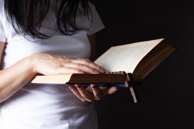 Vrouw bidden met boek en kruis
