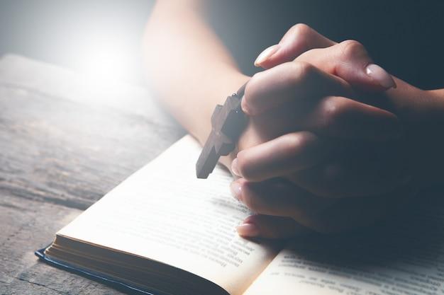 Vrouw bidden op boek houden kruis