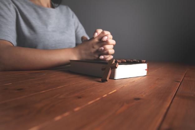 Vrouw bidden op een boek met een kruis
