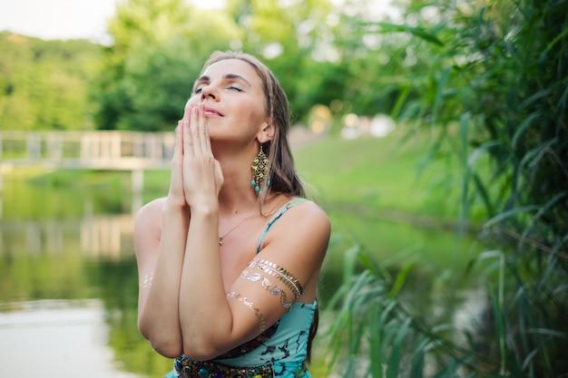 Vrouw bidden portret op groene natuur tijdens prachtige zonsondergang