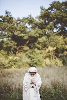 Vrouw bidden terwijl het dragen van een bijbelse mantel