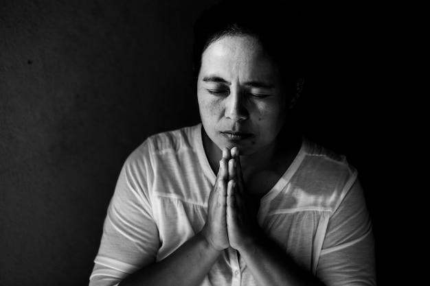 Vrouw bidt met haar ogen dicht